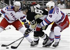 The Pittsburgh Penguins' Sidney Crosby, center, tries to skate past the New York Rangers' Ruslan Fedotenko, right, and Ryan Callahan during the second period. Callahan scored the game-winning goal for the Rangers, who won their third consecutive game.