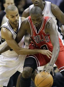 The Spurs' Tony Parker reaches for the ball against the Bulls' Omer Asik during the first quarter on Wednesday. Parker finished with 21 points in the Spurs' win.