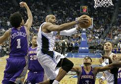 Orlando Magic guard Vince Carter gets around Phoenix Suns shooting guard Josh Childress (1), center Garret Siler (20), and forward Jared Dudley for a shot during the first half on Thursday. Orlando won 105-89.