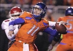 Boise State quarterback Kellen Moore, winding up for a first-half throw against Fresno State, went 27-of-38 for 333 yards, four touchdowns and one interception.