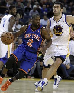 The New York Knicks' Raymond Felton drives ahead of Golden State Warriors' Vladimir Radmanovic during the first half. Felton had a career-high 25 points and the Knicks held off the Warriors 125-119.