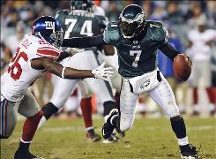 Michael Vick, evading the Giants' Antrel Rolle, threw 24-of-38 for 258 yards and rushed for 35 yards and a touchdown as the Eagles took control of the NFC East.