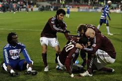 Macoumba Kandji of the Colorado Rapids celebrates his goal with teammates as Ugo Ihemelu of FC Dallas looks on during overtime of the 2010 MLS Cup match at BMO Field on Sunday in Toronto, Canada.