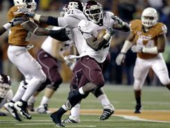 Texas A&M running back Cyrus Gray, center, breaks away for a 48-yard touchdown run against Texas during the third quarter of their game Thursday night. Gray finished with a career-high 223 yards on the ground as the 18th-ranked Aggies beat the Longhorns 24-17.