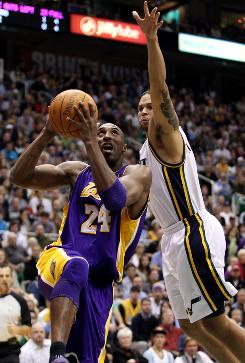 Los Angeles Lakers guard Kobe Bryant goes to the basket as Utah Jazz guard Deron Williams stretches to guard him during the first half on Friday. Williams led the Jazz with 29 points as they handed the Lakers their third loss.