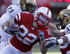 Nebraska running back Rex Burkhead (22) ran for 101 yards and a touchdown, but also threw a pair of TDs in the Cornhuskers' rout of Colorado.