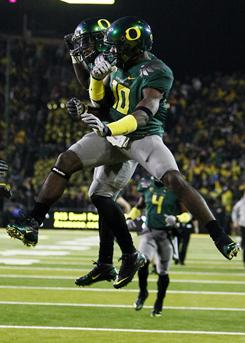 D.J. Davis, front, Kenjon Barner and the Oregon Ducks kept their BCS title hopes alive with a come-from-behind 48-29 win over Arizona.