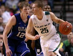 E. J. Singler, right, of Oregon dribbles against his brother Kyle Singler of Duke during their game Saturday at the Rose Garden in Portland, Oregon. The top-ranked Blue Devils came away with a 98-71 victory.