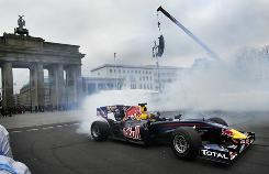 Formula One champion Sebastian Vettel smokes his tires in front of the Brandenburger Gate during a victory tour of Berlin.