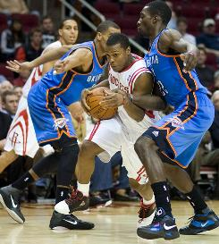 The Houston Rockets' Kyle Lowry drives between Oklahoma City Thunder defenders Thabo Sefolosha, left, and Jeff Green during the first half Sunday.