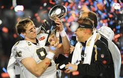 Saints quarterback Drew Brees, left, holds the Lombardi Trophy with coach Sean Payton after New Orleans won the Super Bowl last winter.