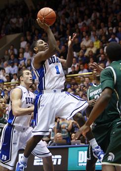 Duke's Kyrie Irving (1) drives for a basket against a pair of Michigan State defenders during the first half of their game Wednesday in Durham, N.C. Irving finished with a game-high 31 points as the top-ranked Blue Devils beat the No. 6 Spartans 84-79.
