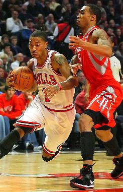 Chicago Bulls point guard Derrick Rose drives past Houston Rockets shooting guard Courtney Lee in the first half on Saturday.  Rose led the Bulls to an overtime win, 119-116.