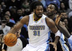 Nuggets center Nene spins around Grizzlies center Hasheem Thabeet during the first half Sunday. Nene finished with 27 points and the Nuggets gave coach George Karl his 999th NBA win.