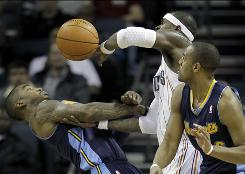 Stephen Jackson, center, battles with the Nuggets' J.R. Smith, left, and Arron Afflalo, right, for a loose ball in the second half on Tuesday. Jackson had 23 points in the Bobcats' 100-98 victory.