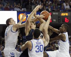 Notre Dame's Tim Abromaitis, center, fights with Kentucky players, from left, Jon Hood, Eloy Vargas (30) and Doron Lamb for a rebound. Tied at 40 at halftime, No. 16 Kentucky surged past No. 23 Notre Dame in the second half and won 72-58.