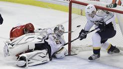 Predators goalie Anders Lindback, center, makes a diving save against the Red Wings during the second period as teammate Marcel Goc guards the net.