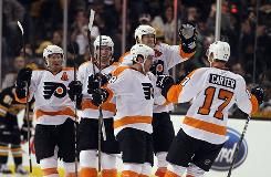 Mike Richards (18) of the Flyers is congratulated by teammates Chris Pronger, Andreas Nodl, Kimmo Timonen and Jeff Carter after Richards scored the game-winning goal in overtime against the Bruins on Saturday. The Flyers defeated the Bruins 2-1.