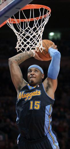 The Denver Nuggets' Carmelo Anthony dunks the ball in the second half on Sunday. The Knicks beat the Nuggets 129-125.