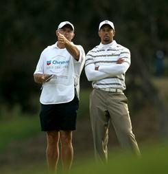 Tiger Woods and caddie Steve Williams talk over his second shot on the 18th hole during the third round of the Chevron World Challenge in Thousand Oaks, Calif.