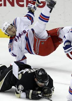 The  Penguins' Matt Cooke, bottom, and the Rangers' Steve Eminger collide during the first period of an NHL game in Pittsburgh on Wednesday.