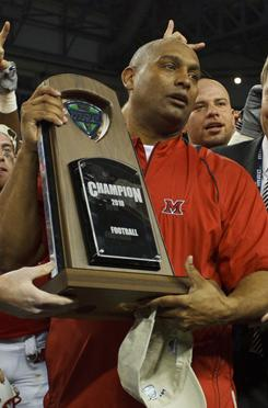 Miami (Ohio) coach Mike Haywood holds the championship trophy after winning the MAC title game against Northern Illinois at Ford Field.