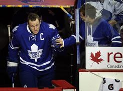 Toronto Maple Leafs captain Dion Phaneuf, left, greets a fan as he takes to the ice in a game against the Flames in Calgary, Canada.