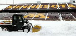 A snow plow takes to the field at TCF Bank Stadium in Minneapolis where the Vikings and Chicago Bears are expected to play on Monday.