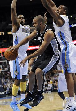 San Antonio Spurs guard Tony Parker passes around Denver Nuggets forward Gary Forbes and Arron Afflalo (6) during the first half on Thursday. The Spurs won 113-112.
