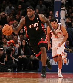 LeBron James of the Miami Heat dribbles as Landry Fields of the New York Knicks gives chase at Madison Square Garden on Friday. James finished with a triple-double and the Heat won 113-91.