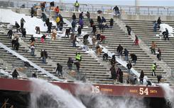 Volunteers remove snow from the stands at TCF Bank Stadium on Friday. Monday night's game between the Vikings and Bears has been moved to the venue, which is on the University of Minnesota's campus.
