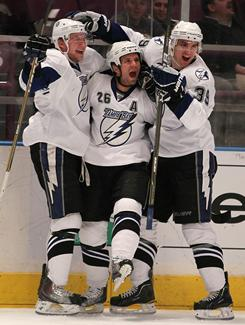 The Lightning's Steven Stamkos, left, Martin St. Louis, center, and Mike Lundin celebrate a goal by St. Louis early in the first period. Stamkos added a goal later in the period.