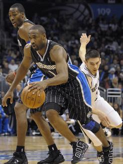 Orlando Magic guard Gilbert Arenas drives past San Antonio Spurs guard Chris Quinn around a Dwight Howard pick during the second half onThursday. The new-look Magic beat the NBA-best Spurs 123-101.