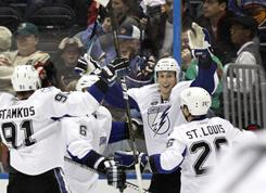 Tampa Bay Lightning center Vincent Lecavalier, second from right, celebrates with teammates after scoring the game-winning goal in overtime of Tampa Bay's 3-2 victory Sunday in Atlanta.