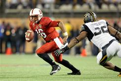 North Carolina State quarterback Russell Wilson, left, is forced out of the pocket by West Virginia linebacker Najee Goode during the second quarter of the 2010 Champs Sports Bowl.