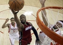 The Miami Heat's Dwyane Wade goes up for a shot as Houston Rockets' Courtney Lee (5) and Brad Miller, right, defend during the fourth quarter on Wednesday. Wade finished with 45 points, and the Heat beat the Rockets 125-119.