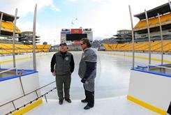 NHL facilites manager Dan Craig talks with NHL facilities supervisor Don Moffatt before painting the ice white for the Winter Classic.