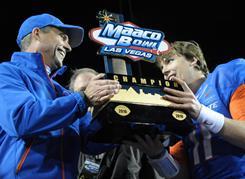 Boise State Broncos coach Chris Petersen, left, and quarterback Kellen Moore celebrate with the MAACO Bowl trophy Dec. 22.