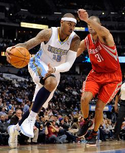Denver forward Carmelo Anthony drives past Houston small forward Shane Battier during the third quarter on Monday. Anthony finished with 33 points, 11 rebounds and five assists and the Nuggets beat the Rockets 113-106.