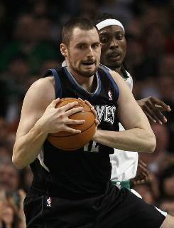 Minnesota's Kevin Love grabs a rebound in front of Boston's Marquis Daniels on Monday. The Celtics beat the Timberwolves 96-93 despite Love's double-digit rebounding effort.