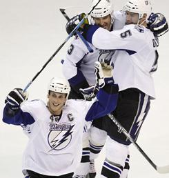 Tampa Bay's Vincent Lecavalier, bottom, Pavel Kubina, top left, and Mattias Ohlund celebrate after the Lightning defeated the Capitals 1-0 in overtime in Washington.