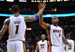 Miami small forward LeBron James (right) celebrates with teammate power forward Chris Bosh during the fourth quarter on Friday. James and Bosh combined for 42 points and the Heat beat the Milwaukee Bucks in overtime 101-95.