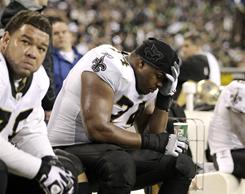 Jonathan Goodwin, left, and Jermon Bushrod sat on a dejected Saints bench late in the team's 41-36 win.