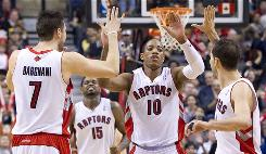 The Toronto Raptors' DeMar DeRozan, second from right, celebrates a basket with teammates, from left to right, Andrea Bargnani, Amir Johnson, and Jose Calderon on Sunday. The Raptors defeated the Kings 118-112.