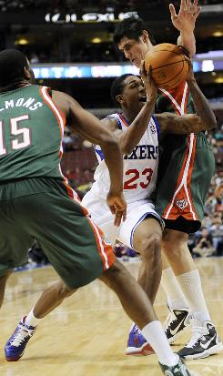 Philadelphia's Lou Williams, center, drives past Milwaukee's John Salmons, left, and Ersan Ilyasova in the second half on Friday. Williams finished with 25 points and the 76ers beat the Bucks 95-94.