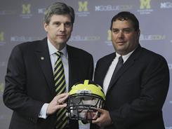Michigan athletic director Dave Brandon, left, stands with new football coach Brady Hoke at the school's news conference Wednesday.