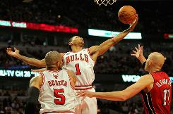 Derrick Rose of Chicago collects a rebound in front of Carlos Boozer of the Bulls and Zydrunas Ilgauskas of Miami on Saturday.  Rose finished with 34 points and the Bulls beat the Heat 99-96.