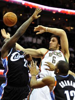 Milwaukee center Andrew Bogut passes under pressure from Cleveland power forward J.J. Hickson (21) and shooting guard Joey Graham (12) during the fourth quarter on Friday. Bogut finished wtih 23 points as the Bucks beat the Cavaliers 102-88.