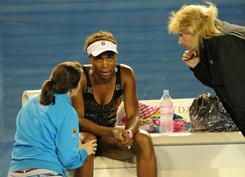 Venus Williams, center, talks with a trainer, left, and a tournament official after sustaining an injury early in her third-round match against Andrea Petkovic of Germany. Williams conceded after just one game.