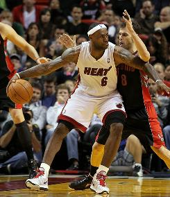 Miami's LeBron James posts up Toronto's Jose Calderon on Saturday. James finished with 38 points and the Heat beat the Raptors 120-103.